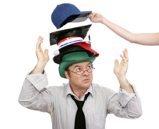 Overwhelmed businessman with more and more responsibility - represented by hats.  Another being added.
